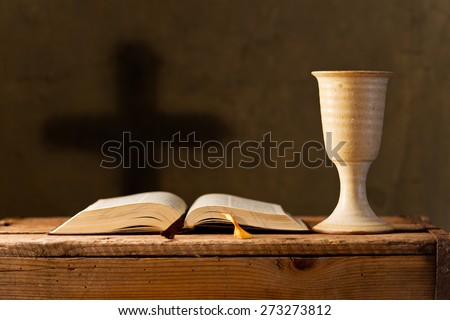 open bible with chalice of wine in the church,selective focus - stock photo