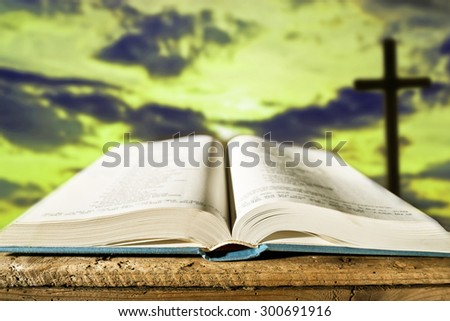 open bible with cross at dusk,  shallow depth of field - stock photo