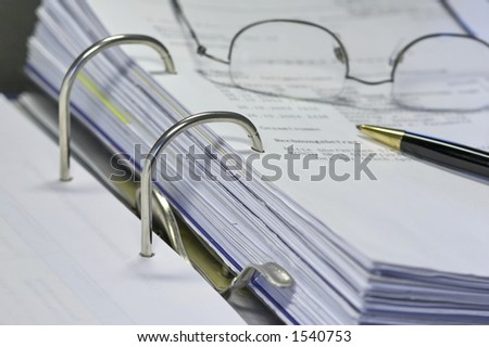 open binder with invoice and office items