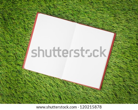 open blank book on artificial green grass