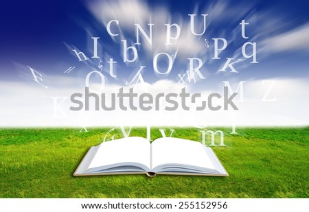 Open blank book with alphabets letter on green filed,nature background