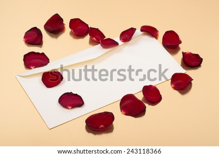 open blank envelope with red leaves in heart shape on top of a gold background - stock photo