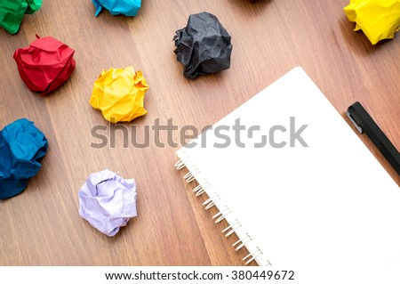 open blank ring binder white book and pencil with group of colorful crumpled paper ball on dark brown table top, Business Brainstorming concept,mock up for adding your text - stock photo