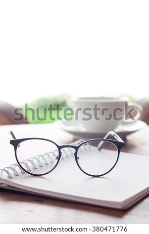 Open blank white notebook and eyeglasses with cup of coffee, stock photo