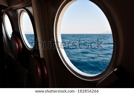 Open boat porthole with ocean view close up  - stock photo