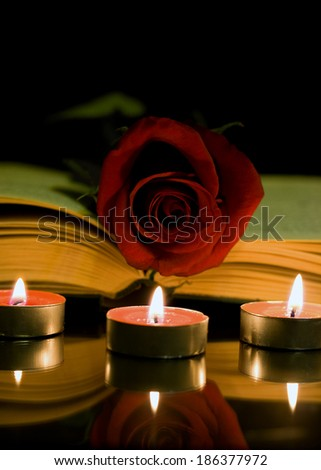 Open book and a red rose and candle on a black background - stock photo