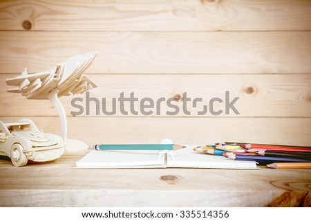 Open book and Colored pencils on wooden table, home decoration concept. - stock photo