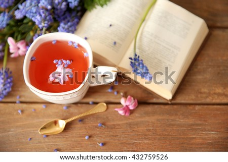 Open book and cup of tea  on wooden table