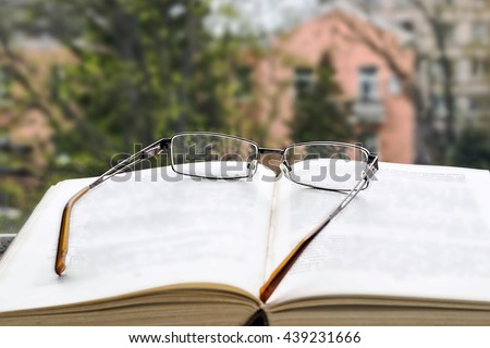 Open book and glasses. View from the window. Reading, learning books.  - stock photo