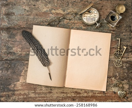 Open book and vintage writing accessories. Feather pen and inkwell on wooden background
