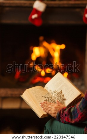 Open book by the burning fireplace. Open story book with a snowflake in front of a cozy warm fireplace decorated for Christmas. Relaxed holidays evening concept.  - stock photo