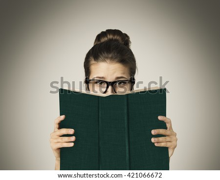 Open Book Hiding Face, Woman Eyes Reading in Glasses on Gray - stock photo