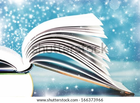 Open book in front of abstract holiday background - stock photo