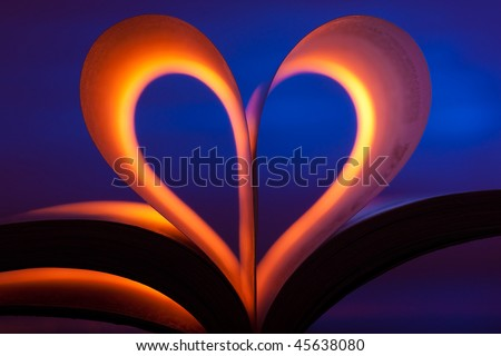 Open book in red heart shape on blue background - stock photo