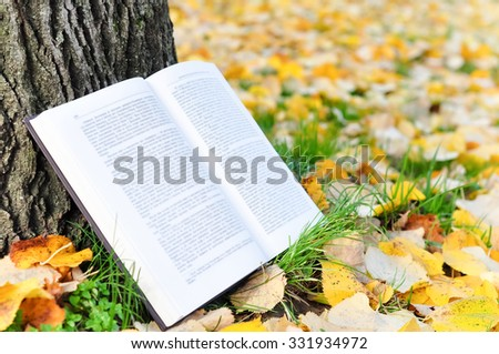 Open book leaning on a tree outdoor in a park
