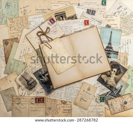 Open book, old letters and postcards. Used paper background. Travel memories scrapbook for France and Paris