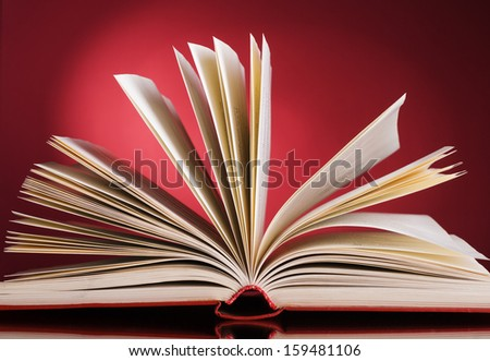 Open book on a red background. - stock photo