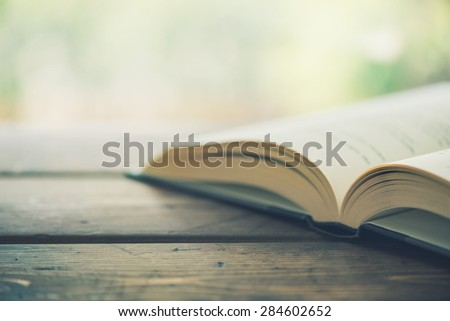 Open book on a wooden desk up close - Split toned - stock photo