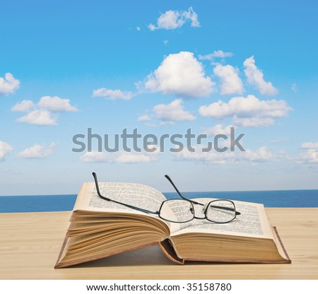 Open book on desk and sea