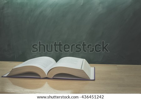 open book on Green chalkboard,education concept