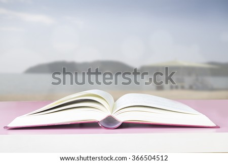 Open book on pink table with green bokeh abstract background
