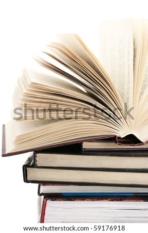 Open book on stack of various books against white background. - stock photo