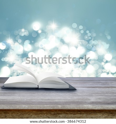 Open book on table in front of abstract background
