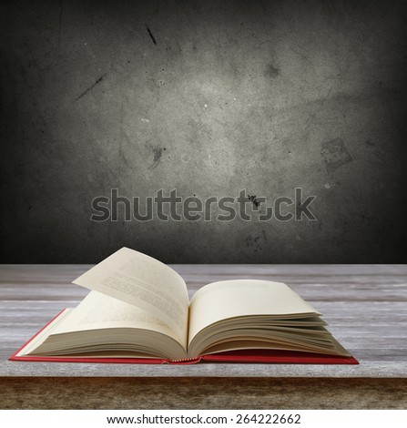 Open book on table in front of grey wall