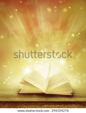 Open book on table in front of magical background - stock photo