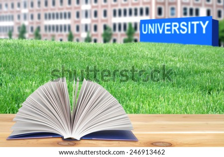 open book on the wooden table in the university campus - stock photo