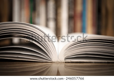 Open book on the wooden table with defocused books in the background - stock photo