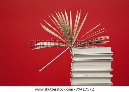 Open book on top of a group of white books - stock photo