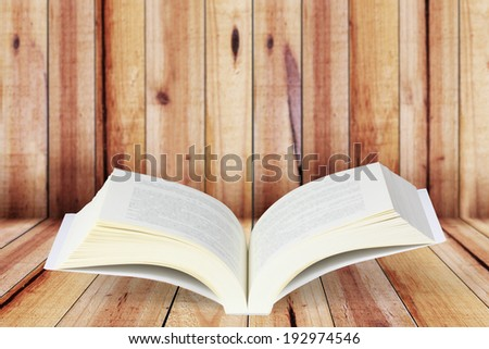 Open book on wood planks background