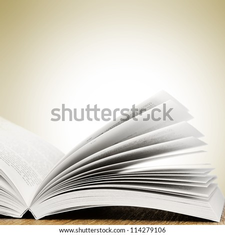 Open book on wood table over white background. With place for text - stock photo
