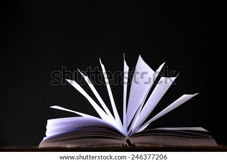 Open book on wooden surface and dark background