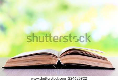 Open book on wooden table on natural background - stock photo