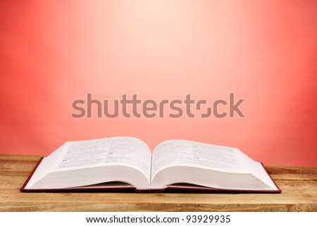 Open book on wooden table on red background - stock photo