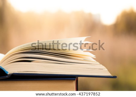 Open book over the blurred landscape background - stock photo