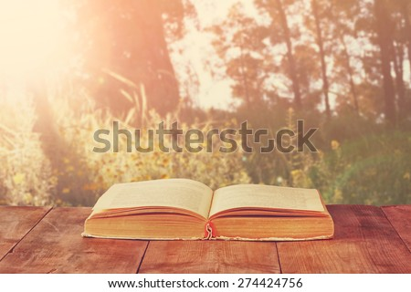 open book over wooden rustic table in front of wild landscape and sunset light burst  - stock photo