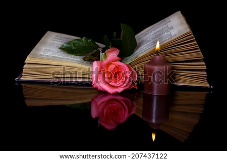 Open book, Rose and a burning candle on a black background - stock photo