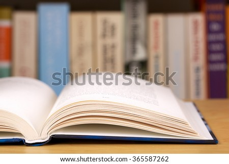 Open book with a row of books in the background