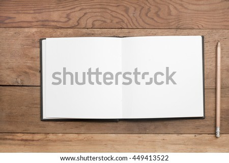 Open book with blank pages and pencil on wood table. - stock photo
