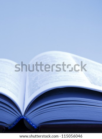 Open book with blurred pages (in blue tones) - stock photo