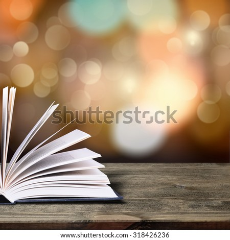 Open book with bokeh light on dark abstract background - stock photo