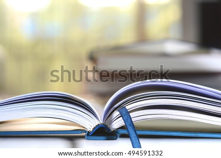 Open book with fanned out pages on a white background.