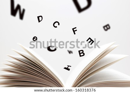 Open Book with flying letters - stock photo