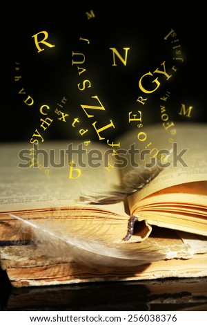 Open book with flying letters on table on dark background - stock photo