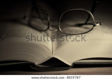 Open book with glasses in dark environment