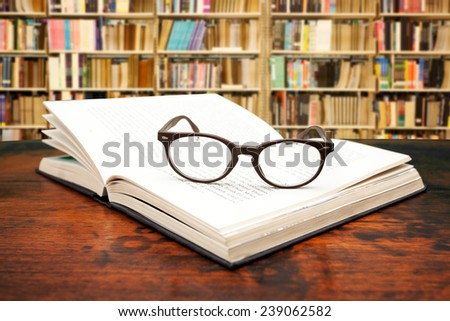 Open book with glasses on the desk against library