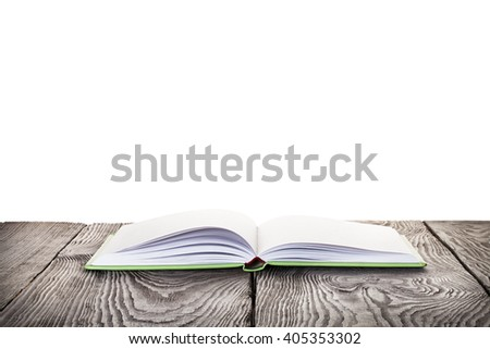 Open book with green cover on wooden table isolated on white background